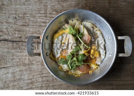A Thai pan fire egg cooking with pork and vegetable on the wooden desk. - stock photo