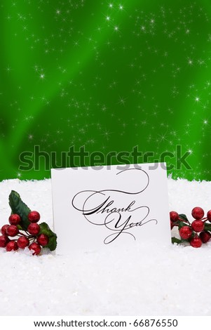 A thank you card sitting on snow with a green background - stock photo