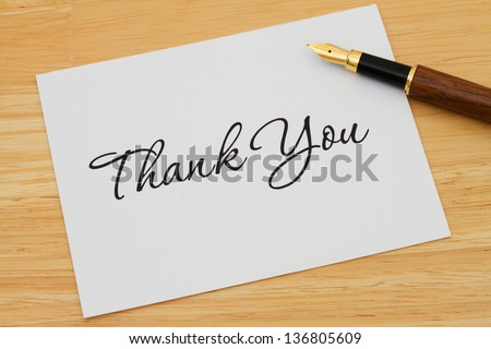A thank you card with a fountain pen on a wooden desk, Writing a Thank You Note - stock photo