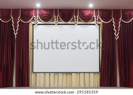 A theater stage with a red curtain, and a project board. - stock photo