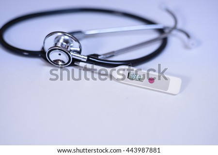 A thermometer and stethoscope, thermometer displaying 103,0 F fever. For Celsius please see Image ID:443301637 - stock photo