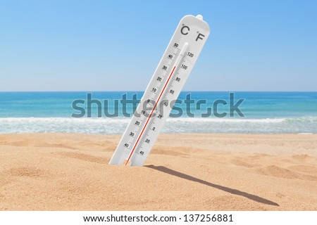 A thermometer on the beach near the sea to check the temperature. - stock photo