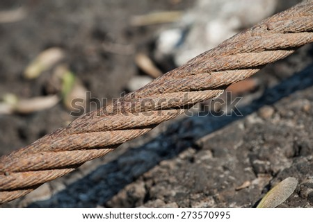 A thick, abandoned cable used to moor barges or other large vessels reaches over the shore of the mighty Mississippi River. - stock photo