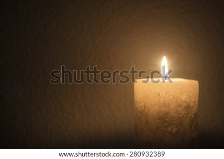 A thick candle burns brightly in dark room - landscape interior - stock photo