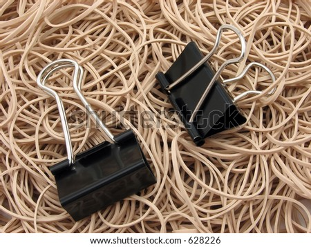A thick collection of rubber bands with two butterfly binder clips sitting on them - stock photo