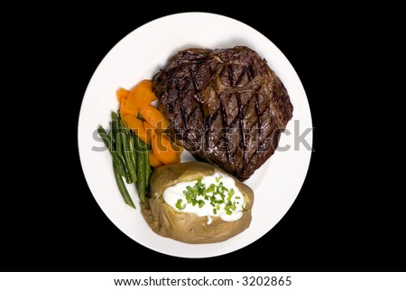 A thick juicy Rib Eye steak dinner with a baked potato - stock photo