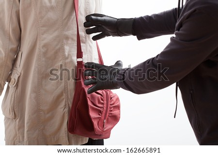 A thief in leather gloves about to steal a red bag - stock photo