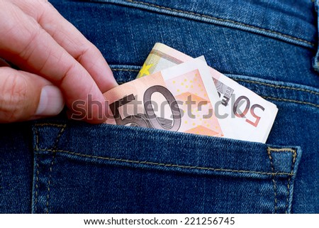 a thief pulls money out of a back pocket - stock photo