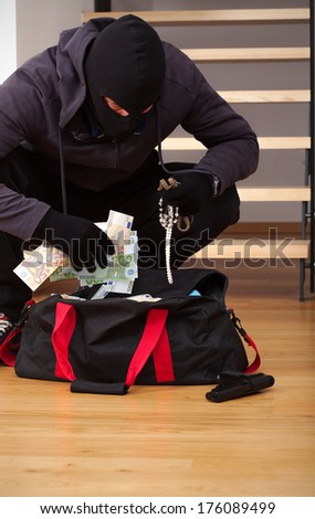 A thief searching a bag with stolen goodies - stock photo
