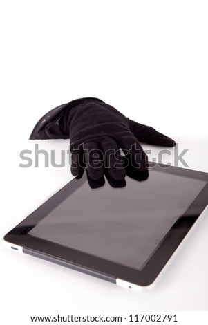 A thief stealing a tablet computer - piracy concept - stock photo