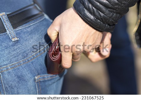 A thief stealing a wallet from his back pocket a careless person. The risk of theft - stock photo