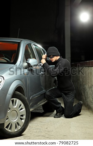 A thief wearing a robbery mask trying to steal a car