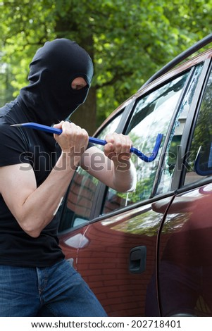 A thief with crowbar breaking into a car - stock photo