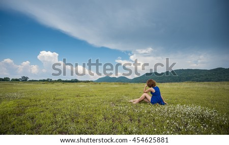 A thinking woman sitting on the grass with mountain view