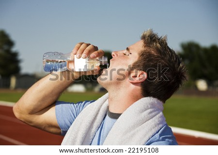 A thirsty athlete splashes some water down his throat after running a race.