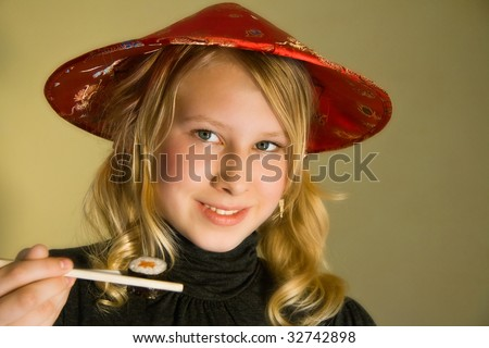 a thirteen years old girl at a sushi-bar with chopsticks - stock photo