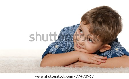 A thoughtful boy is dreaming on the carpet; isolated on the white background - stock photo