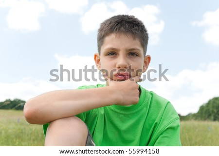 A thoughtful  boy is sitting on the grass against the sky - stock photo