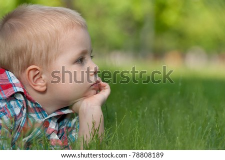 A thoughtful little boy is lying on the green grass