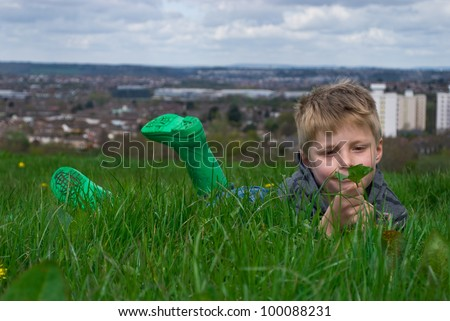 A thoughtful little boy looking at a leaf in the countryside, with a view of the city in the background. - stock photo