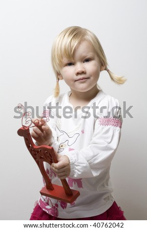 A thoughtful little girl holding a red toy reindeer christmas present.