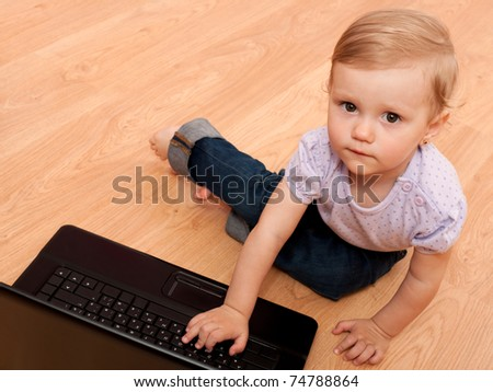 A thoughtful little girls is discovering a laptop on the floor - stock photo