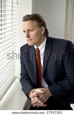 A thoughtful looking businessman sitting next to a window.