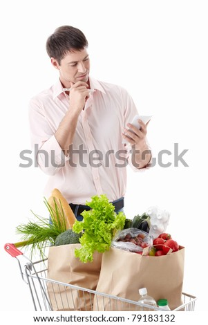 A thoughtful man with a cart with food on a white background