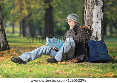 A thoughtful young student seated on a green grass reading a book in the park - stock photo
