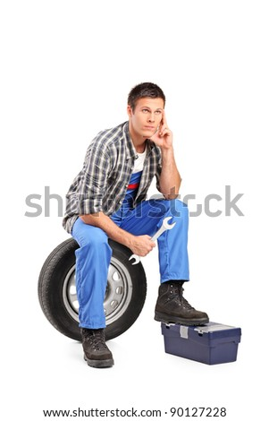 A thoughtfull mechanic sitting on a spare tire and holding a wrench isolated on white background - stock photo