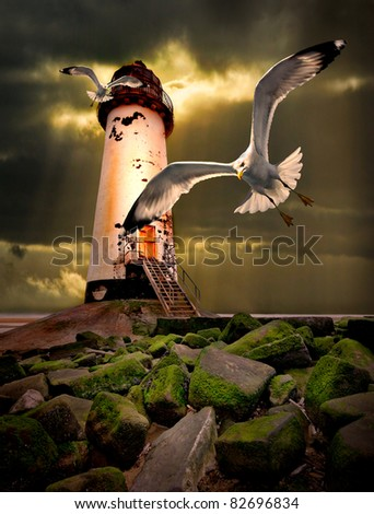 a threatening moody image of an abandoned lighthouse on the north wales coast with herring gulls swooping inshore and a stormy sky with sunbeams beyond. - stock photo