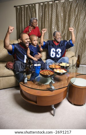 A three generation African-American family cheering and watching football game together on tv. - stock photo