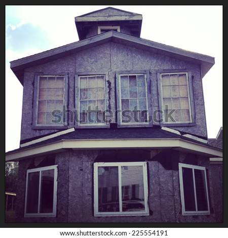 A three level house with the siding stripped off to the bare wood. - stock photo