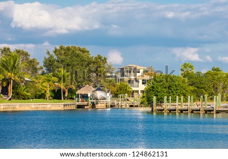 A three-story luxury house with a boat lift on a canal in Southwest Florida, USA, surrounded by oak trees, palm tress and lush lawns. - stock photo