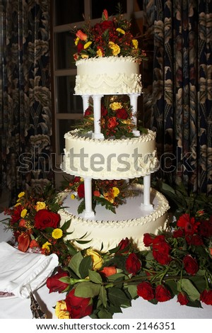 a three tiered yellow wedding cake with roses - stock photo