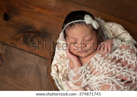 A three week old newborn baby girl sleeping in a little, wooden bowl. She is wearing a cream colored bow headband and swaddled with a decorative wrap. Shot in the studio on a wood background. - stock photo