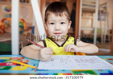 A three year boy in the yellow T-shirt with hood sits at the table, drawing and writing letters with color pencils, looking straight at the camera, interested gaze. - stock photo