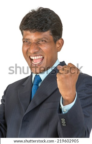A thrilled Indian / South Asian business executive in a suit cheering a win or victory with a big shout and clenched fist. Isolated on white background. - stock photo