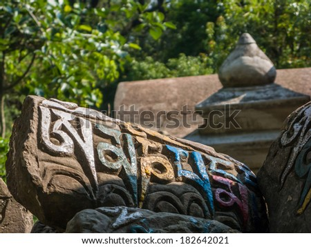 A Tibetan buddhist prayer carved into a stone and painted. - stock photo