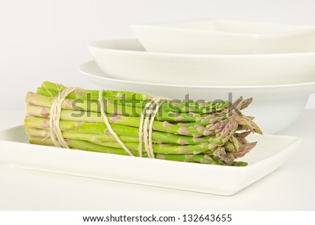A tied bundle of asparagus on a white plate with bowls in background - stock photo