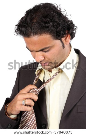 A tied Indian businessman removing his tie, on white studio background. - stock photo