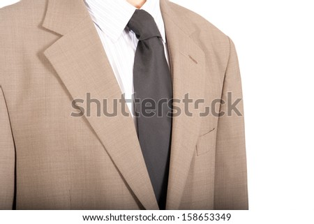 A tightly focused shot of a white pinstrip shirt, beige suit and black tie. Anonymous and ageless wearer as this is a classic style. - stock photo