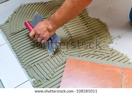 a tiler at work. bonding of floor tile with tile adhesive and filler. - stock photo