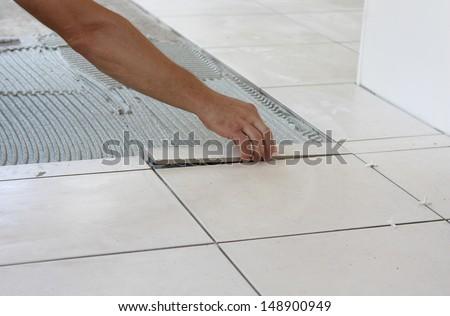 a tiler laying a new tiles to an outdoor patio - stock photo