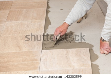 a tiler laying a tiled marble