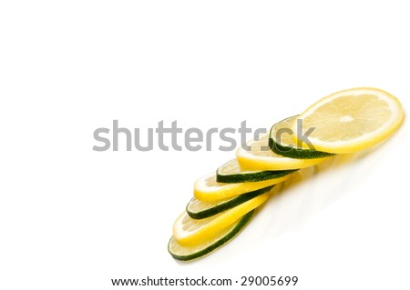 A tilted  horizontal close-up of juicy fresh cut lemon and lime slices with space for copy - stock photo
