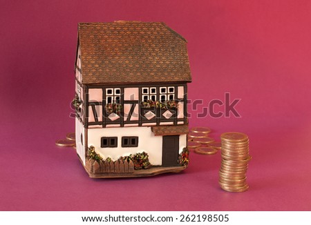 A timber house and a pile of euros on a purple background - stock photo