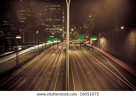 A time exposure shot of downtown buildings and traffic at night in monochrome