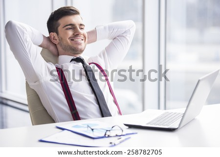 A time for relax. Young, happy businessman is relaxing in his office. - stock photo