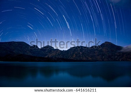 A time lapse exposure showing star trails over the crater lake at Mount Rinjani, Indonesia's second largest active volcano. Astrophotography at the segara anak at Gunung Rinjani, Lombok, Indonesia.